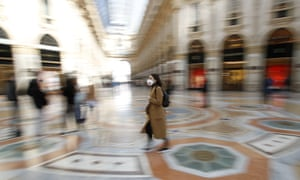 A woman wears a mask as she walks in Milan.