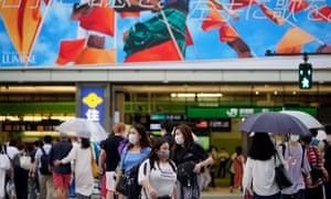 Pedestrians wearing face masks in front of Shinjuku station in Tokyo