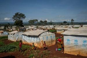Burundian refugees stand among makeshift shelters in Nyarugusu camp
