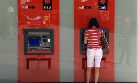 A customer uses an ATM machine outside National Australia Bank in Sydney.