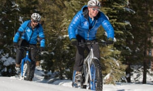 Two male riders in blue jackets cycle on fatbikes in the snow at Tahoe Donner, California. US.