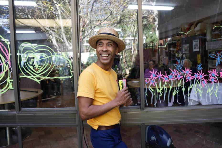 Musician and actor Benhur Helwend creating window art at the Whiddon aged care home in Sydney's north shore.