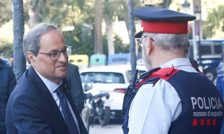 Quim Torra is welcomed by a policeman upon his arrival in Barcelona.