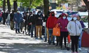 People wait in line as members of the US Army National Guard hand out food and other essentials for people in need in Brooklyn, New York.