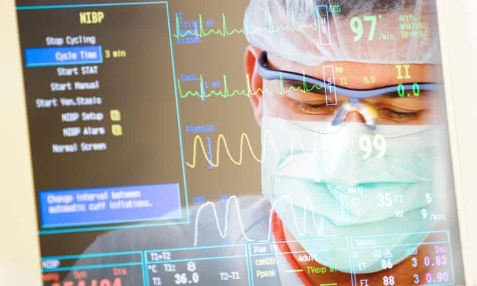 A doctor looks at a patient's readings on a health monitor.