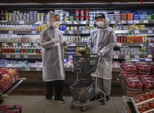A couple wear plastic coats and protective masks as they shop for groceries at a supermarket in Beijing, China following the outbreak of coronavirus in the country.