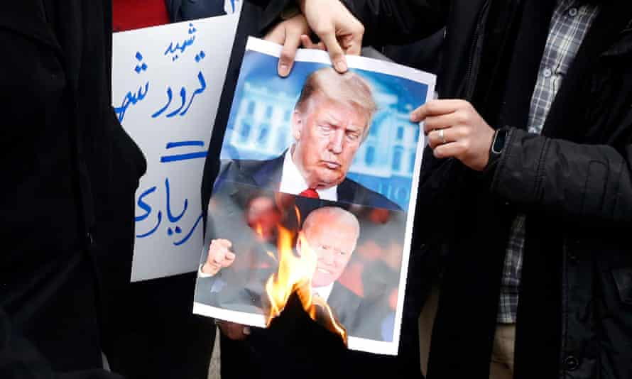 Iranian students burn a picture of Donald Trump and Joe Biden at a protest in Tehran over the killing of Mohsen Fakhrizadeh-Mahabadi.