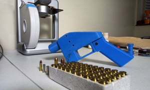 A pistol next to the 3D printer on which its components were made.