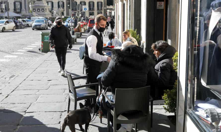 A waiter serves customers outside a cafe in Naples on Tuesday. Italy has been plunged into a political crisis after the resignation of Giuseppe Conte as it attempts to deal with the pandemic.