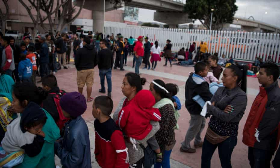 Central American migrants stand in line for blankets for their overnight stay at the San Ysidro border crossing in Tijuana, Mexico.