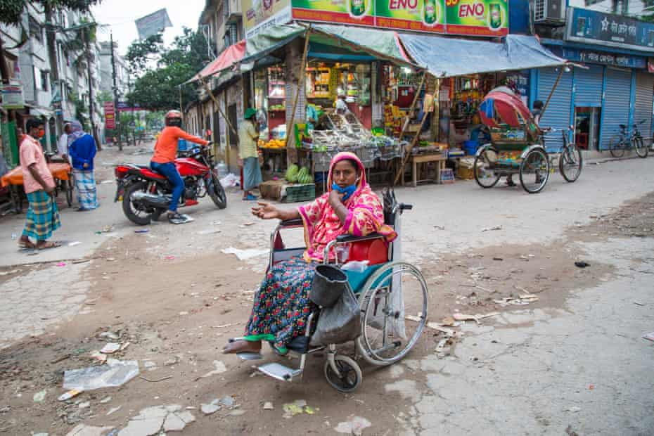 A woman in wheelchair begs in the street