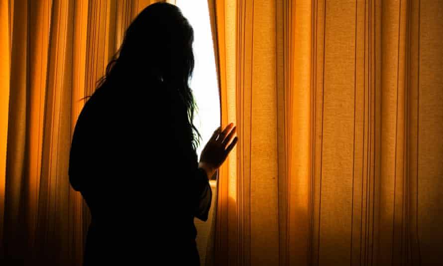 Woman looks through gap in curtains