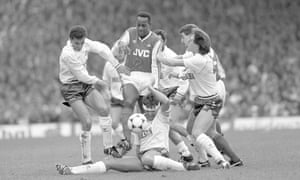 Michael Thomas steps over the tackle of Gary Mabbutt during Arsenal's win over Tottenham in March 1988