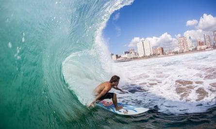 a surfer rides a summer cyclone wave at New Pier beach, Durban.