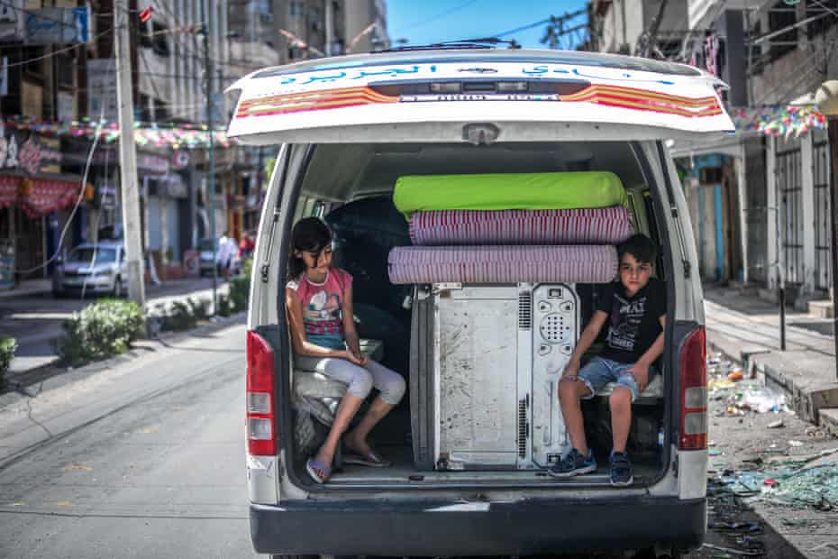Palestinian children sit in the back of a van loaded with salvaged belongings from their home at the al-Jawhara Tower in Gaza City, which was heavily damaged in Israeli airstrikes.