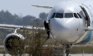 A man climbs out of the cockpit window of the hijacked Egyptair plane.