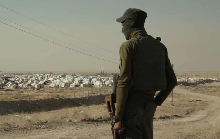 Guard looks over Jabal Baghuz, or Baghuz Mountain, in a-Hawl camp.