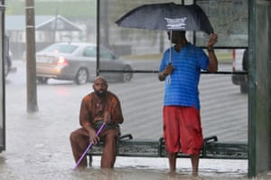 Residents sit under a bus shelter along a flooded Broad Street as heavy rain falls in New Orleans, on 10 July.