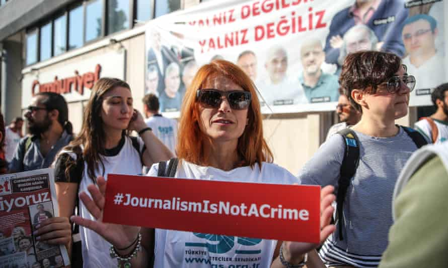 A protester holds up a banner during a protest against the trial of staff from Cumhuriyet newspaper in Turkey