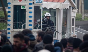 A Greek border guard observes people on the Turkish side of a border crossing