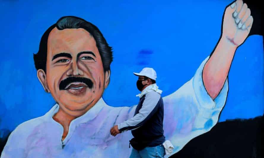 A man walks by a mural depicting President Daniel Ortega in Managua.