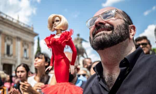 A man holds a doll of Raffaella Carrà