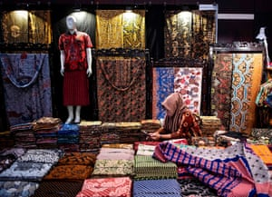 A woman waits for customers surrounded by various batik, traditional Indonesian fabric at a booth during an exhibition in East Java