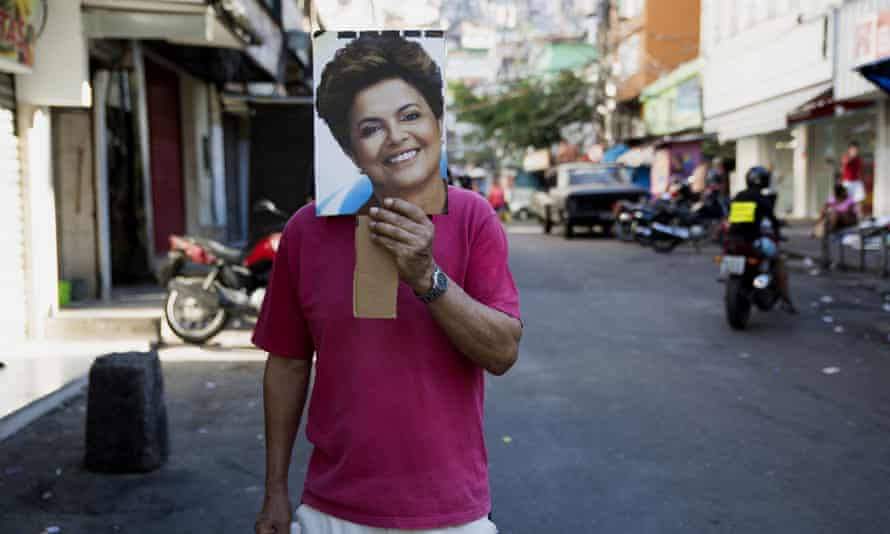An anti-impeachment protester in Rocinha holds a photograph of President Dilma Rousseff