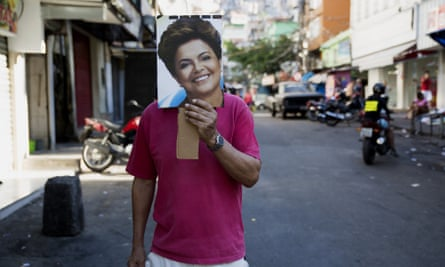 A anti-impeachment protester in Rocinha holds a photograph of President Dilma Rousseff.