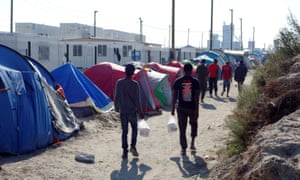 Migrants walk in the northern area of the Calais refugee camp.