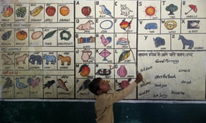 A schoolboy reads from illustrations painted on a wall in a school in Allahabad, India.
