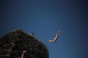 A person dives into the sea as people enjoy the hot weather on Brighton beach.