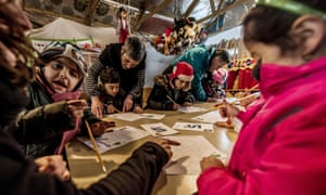 Migrant children attend a lesson in a makeshift school at the camp in Calais, on 10 February 2016.