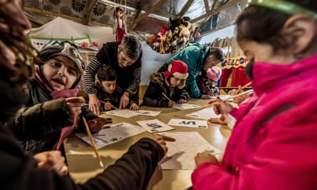 Children attend a lesson in a makeshift school in the migrant camp.