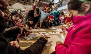 Migrant children attend a lesson in a makeshift school in a migrant camp in Calais