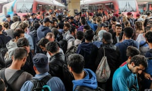 Refugees wait for the train