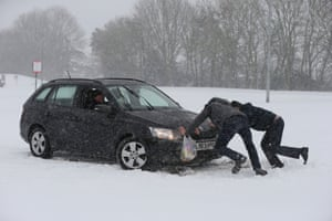 Two people help a driver try to get their car moving at Membury services on the M4