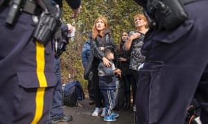 A family from Colombia is detained by Royal Canadian Mounted Police officers after they illegally crossed the border near Hemmingford, Quebec.