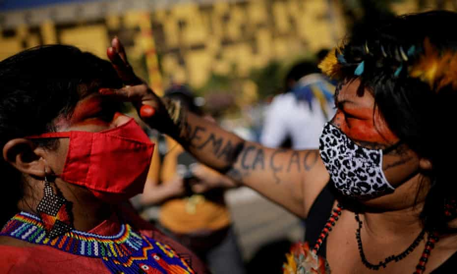 Sônia Guajajara is painted on her face by fellow indigenous leader Alessandra Munduruku during a protest for land demarcation and against President Jair Bolsonaro's government in Brasília in June.