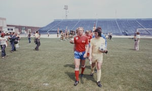 Former England captain Bobby Moore, who was playing for the San Antonio Thunder in the NASL, walks out at JFK Stadium with Gerry Francis of England.