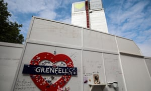 """Mocked-up tube sign reading """"Grenfell"""" on wall beneath tower"""