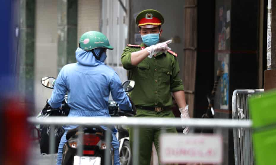 A police officer talks to a woman at the barricaded entrance of an alley where one of the residents is suspected to have Covid-19 in Hanoi, Vietnam.