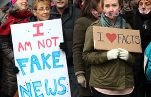 Protesters hold placards saying 'I am not fake news' and 'I love facts'
