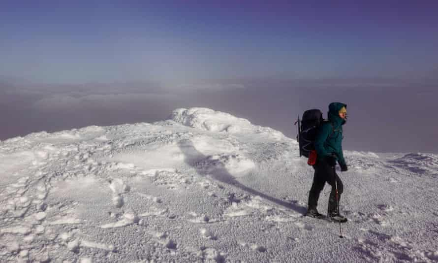 A Munro-bagger reaches the peak of Ben More in the Highlands amid wintry weather.