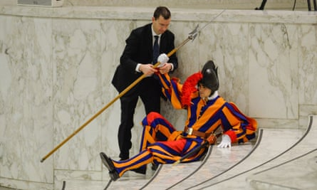 Let me help you: a man helps a Swiss Guard to stand up after stumbling during Pope Francis's weekly general audience at the Vatican.