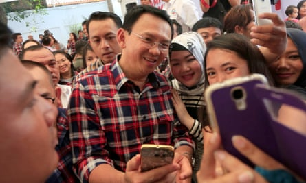 Jakarta Governor Basuki Tjahaja 'Ahok' Purnama takes selfies with his supporters. He has been named a suspect in a case of blasphemy against Islam.