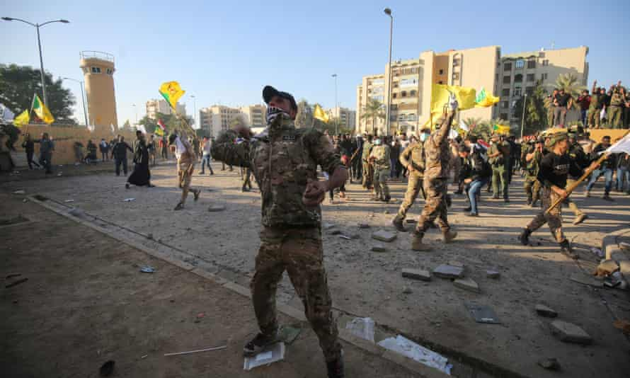 Iraqi supporters hurl stones at the US diplomatic mission in Baghdad on Tuesday, as they rally in anger over weekend air strikes that killed pro-Iran fighters in western Iraq.
