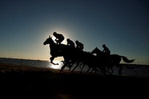 Jockeys ride during a traditional race along the beach at sunset in Sanlúcar de Barrameda, Spain