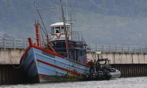 Maritime police officers near a boat which arrived in Langkawi, Malaysia, on Tuesday.