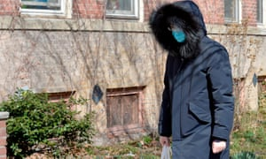 A person wearing a mask walks down a street a day after 60 people were brought to nearby hospitals to be tested for coronavirus, in Boston, Massachusetts.
